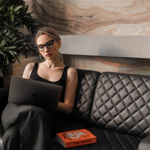 woman in black tank top wearing sunglasses sitting on black leather couch
